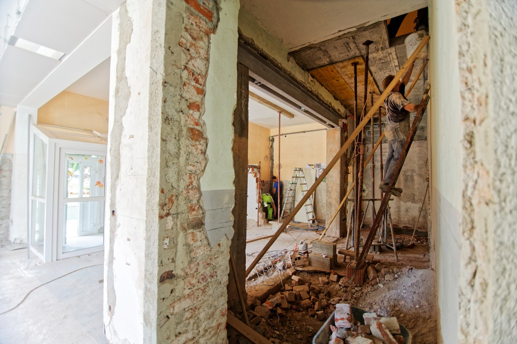 photo of home renovation workers working on a ladder inside the house