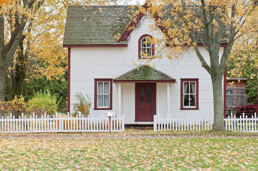 photo of a bungalow house surrounded by trees, white wooden fence