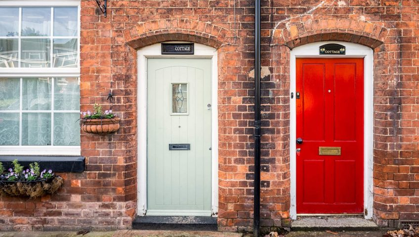 Red and Chartwell Green composite doors with brick wall