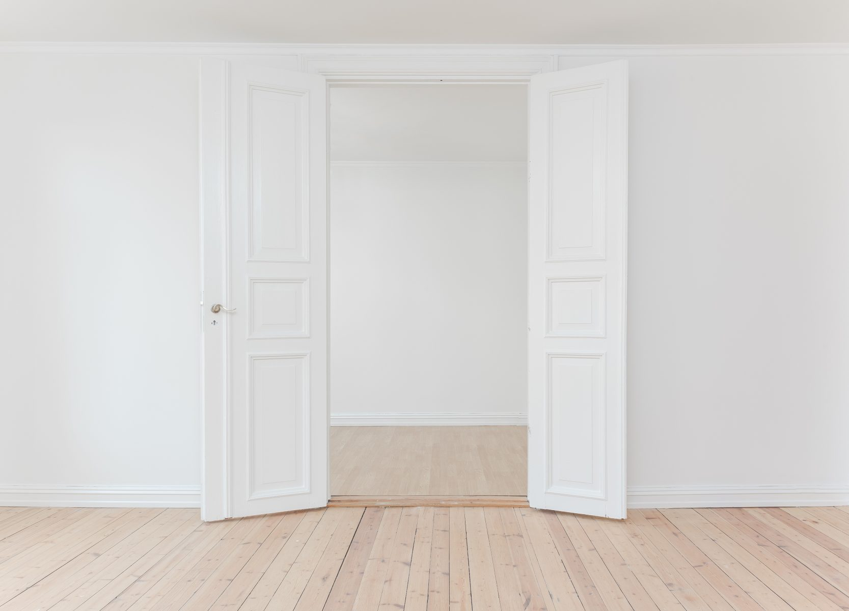 photo of an wide open white door, wood floor and white wall - home renovation tips